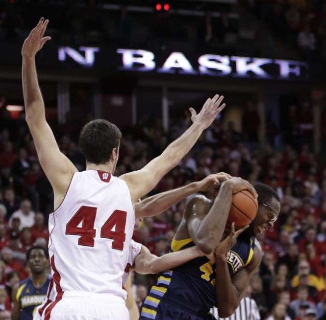 Marquette's Chris Otule, right, grabs an offensive rebound away from Wisconsin's Frank Kaminsky (44) and Josh Gasser, behind, during the first half of an NCAA college basketball game Saturday, Dec. 7, 2013, in Madison, Wis. (AP Photo/Andy Manis)