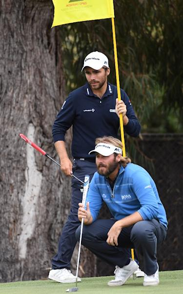 Victor Dubuisson of France (R) and his teammate Romain Langasque line up a putt during the final day of the World Cup of Golf in Melbourne (AFP Photo/William West)