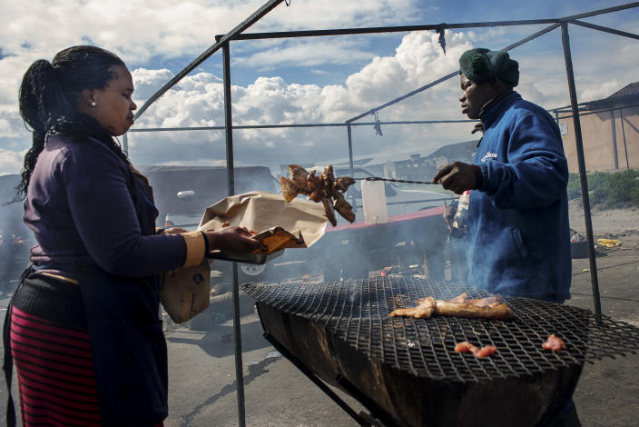 <p>A woman buys meat as a snack, on the street in Khayelitsha is one of the poorest areas of Cape Town. (Photograph by Silvia Landi) </p>