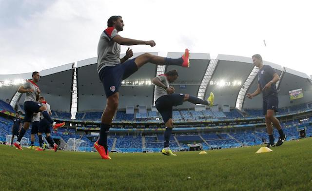 In this photograph taken with a fisheye lens, United States players warm up during an official training session the day before the group G World Cup soccer match between Ghana and the United States at the Arena das Dunas in Natal, Brazil, Sunday, June 15, 2014. (AP Photo/Julio Cortez)