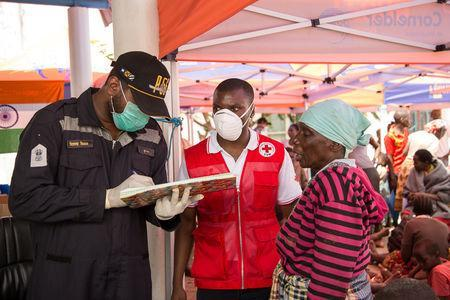 Rescue workers talk with a survivor of Cyclone Idai, at an evacuation centre in Beira, Mozambique, March 21, 2019. Denis Onyodi/Red Cross Red Crescent Climate Centre/Handout via REUTERS
