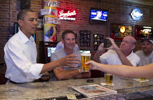 FILE - In this Aug. 14, 2012 file photo, President Barack Obama stops for a beer at The Pump House, a pub and grill, in Cedar Falls, Iowa. Obama and his team frequently talk about the president's fondness for beer, and Obama has been photographed many times downing a beer, including an appearance at the Iowa State Fair last month. Being identified as a beer drinker is an easy way for Obama to connect with votes and serves as a not-so-subtle reminder that his Republican rival Mitt Romney, a Mormon, doesn't drink. (AP Photo/Carolyn Kaster, File)