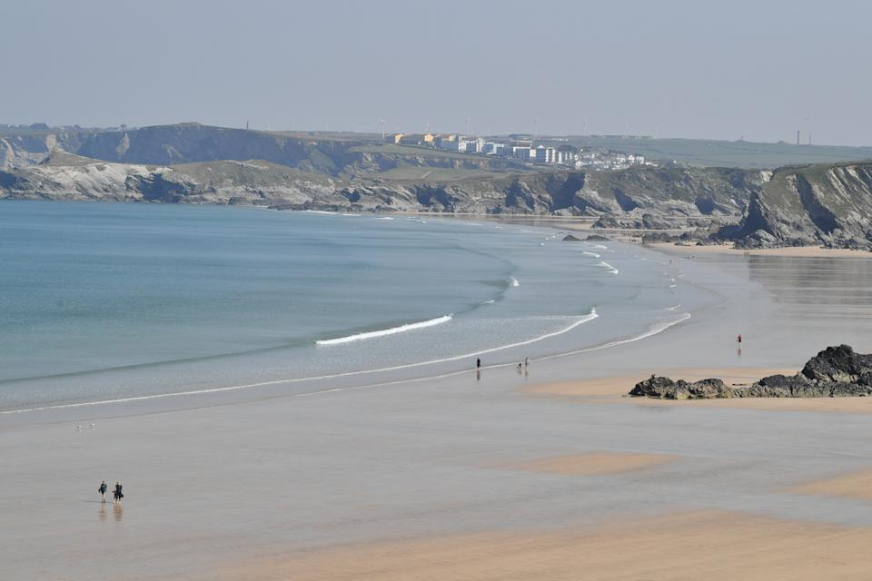 People walk on the Tolcarne beach in Newquay on the north coast of Cornwall, as the UK continues in lockdown to help curb the spread of the coronavirus.