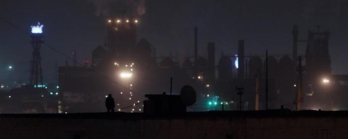 """Andriy Rymaruk silhouetted at night against an industrial backdrop in the movie """"Atlantis."""""""