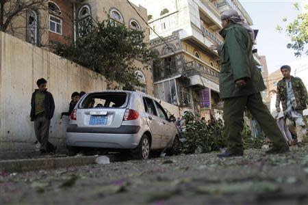 A police trooper (2nd R) guards the site of an explosion in Sanaa February 3, 2014. REUTERS/Khaled Abdullah