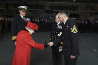 Britain's Queen Elizabeth II presents the 15 years long service and good conduct medal to Petty Officer Matthew Ready, during a visit to the HMS Queen Elizabeth at HM Naval Base, ahead of the ship's maiden deployment, in Portsmouth, England, Saturday May 22, 2021. HMS Queen Elizabeth will be leading a 28-week deployment to the Far East that Prime Minister Boris Johnson has insisted is not confrontational towards China. (Steve Parsons/Pool Photo via AP)