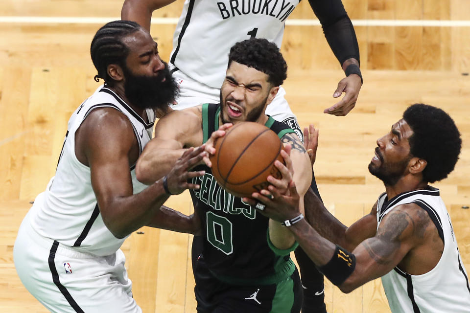 BOSTON, MA - MAY 28:  Jayson Tatum #0 of the Boston Celtics drives to the basket while guarded by James Harden #13 and Kyrie Irving #11 of the Brooklyn Nets during Game Three of the Eastern Conference first round series at TD Garden on May 28, 2021 in Boston, Massachusetts. NOTE TO USER: User expressly acknowledges and agrees that, by downloading and or using this photograph, User is consenting to the terms and conditions of the Getty Images License Agreement. (Photo by Adam Glanzman/Getty Images)