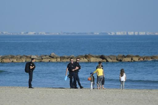 Inhabitants of rural areas are afraid people fleeing big cities such as Paris will widen the virus spread and put pressure on scarce local resources -- here police control a family on a beach in the southern resort of Carnon