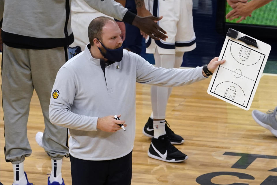 Memphis Grizzlies Taylor Jenkins holds the play board during a timeout in the first half of an NBA basketball game against the Minnesota Timberwolves, Wednesday, Jan. 13, 2021, in Minneapolis. (AP Photo/Jim Mone)
