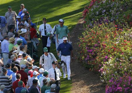 U.S. golfer Bubba Watson (C) and Australia's John Senden walk down the sixth hole during the third round of the Masters golf tournament at the Augusta National Golf Club in Augusta, Georgia April 12, 2014. REUTERS/Brian Snyder