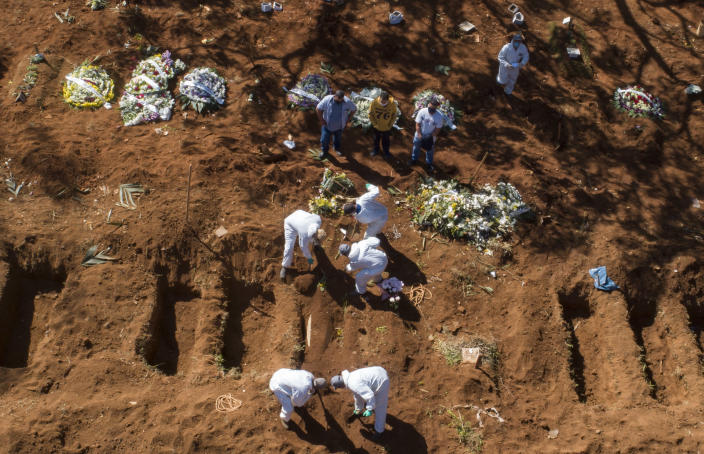FILE - In this May 20, 2020, file photo, cemetery workers in protective clothing bury a COVID-19 victim at the Vila Formosa cemetery in Sao Paulo, Brazil. Even amid a global pandemic, there's no sign that corruption is slowing down in Latin America. In Brazil, which has the world's second-highest number of confirmed cases, police created a task force to investigate crimes tied to the pandemic. (AP Photo/Andre Penner)