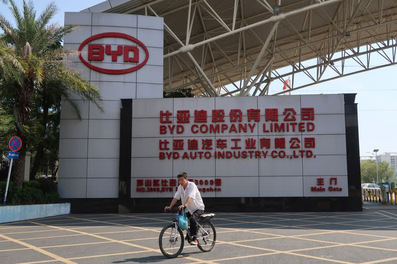 Man cycles past an entrance to the headquarters of Chinese electric car maker BYD in Shenzhen