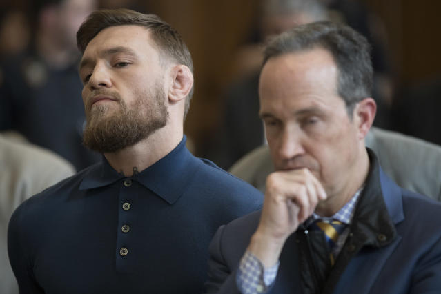 Conor McGregor (L) stands with his lawyer Jim Walden during his arraignment in Brooklyn Criminal Court on Friday in New York. McGregor is facing criminal charges in the wake of a backstage melee. (AP)