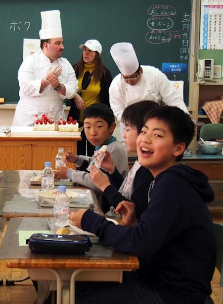 Pupils eat French cuisine and cakes cooked by French chef Christoph Paucod (back L) for their lunch at an elementary school in Koriyama, on December 9, 2013