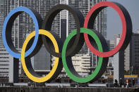 FILE - In this Dec. 1, 2020, file photo, the Olympic Symbol is reinstalled after it was taken down for maintenance ahead of the postponed Tokyo 2020 Olympics in the Odaiba section, in Tokyo. The official cost of the postponed Tokyo Olympics has increased by 22%, the local organizing committee said Tuesday, Dec. 22, 2020, in unveiling its new budget. (AP Photo/Eugene Hoshiko, File)