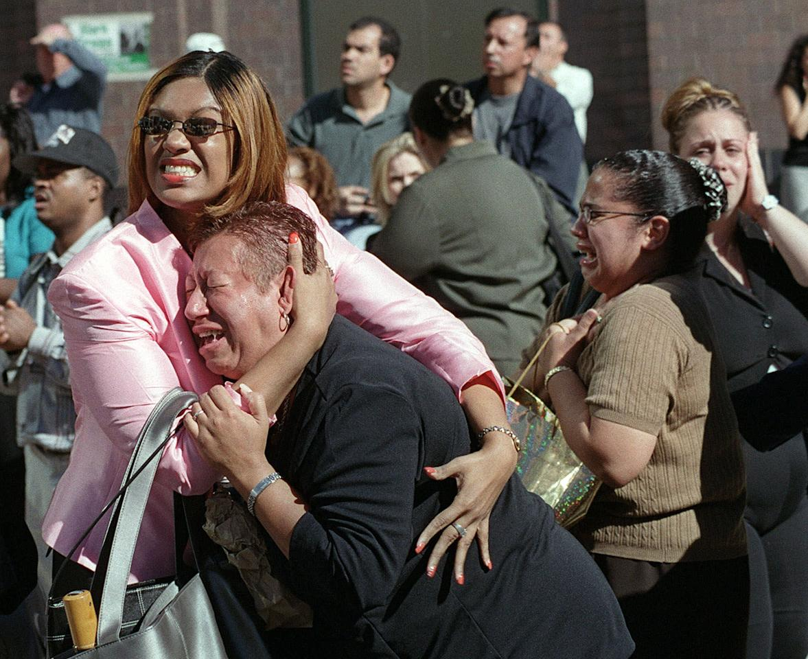 Two women hold each other as they watch the World Trade Center burn following a terrorist attack on the twin skyscrapers in New York Tuesday, Sept. 11, 2001. Terrorists crashed two planes into the World Trade Center and the twin 110-story towers collapsed Tuesday morning. (AP Photo/Ernesto Mora)