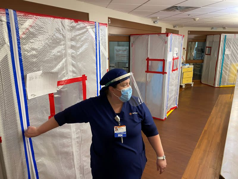 Nurse Katelyn Sofley stands at the entrance to a negative pressure ICU hospital room, where COVID-19 patients are treated, at St John's Regional Medical Center in Oxnard