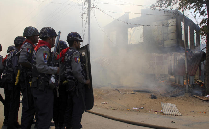 In this Thursday, March. 21, 2013 photo, armed Myanmar police oficers provide security around a smoldering building following ethnic unrest between Buddhists and Muslims in Meikhtila, Mandalay division, about 550 kilometers (340 miles) north of Yangon, Myanmar. Burning fires from two days of Buddhist-Muslim violence that killed at least 20 people smoldered across a central Myanmar town Friday as residents cowered indoors amid growing fears the country's latest bout of sectarian bloodshed could spread. The government's struggle to contain the unrest in Meikhtila is proving another major challenge President Thein Sein's reformist administration as it attempts to chart a path to democracy after nearly half a century of military rule that once crushed all dissent. (AP Photo)
