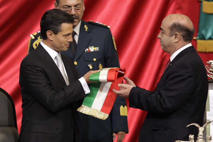 Enrique Pena Nieto, left, receives the presidential sash from Jesus Murillo Karam, president of the lower house, during the presidential inauguration ceremony at the National Congress in Mexico City, Saturday, Dec. 1, 2012. Pena Nieto took the oath of office as Mexico's new president on Saturday, bringing the old ruling party back to power after a 12-year hiatus amid protests inside and outside the congressional chamber where he swore to protect the constitution and laws of the land. AP Photo/Alexandre Meneghini)