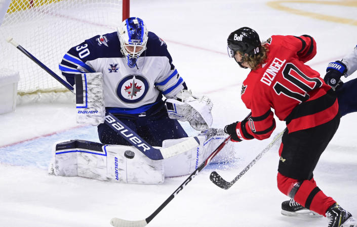 Winnipeg Jets goaltender Laurent Brossoit (30) makes a save on Ottawa Senators' Ryan Dzingel (10) during the second period of an NHL hockey game Wednesday, April 14, 2021, in Ottawa, Ontario. (Sean Kilpatrick/The Canadian Press via AP)