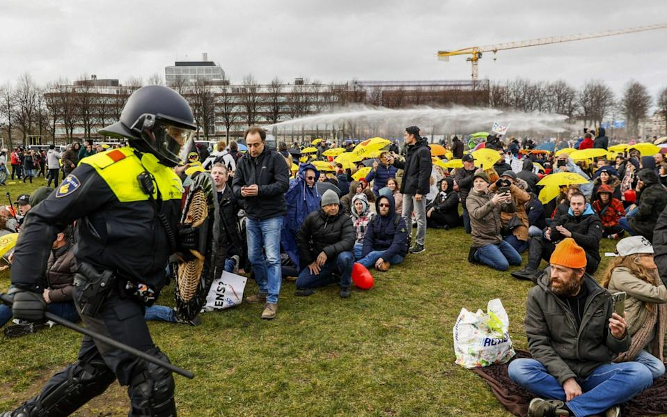 Police officers try to disperse anti-lockdown protesters at the Malieveld in The Hague - Shutterstock