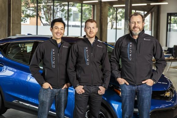 Kan, Vogt, and Amman are shown standing in front of a blue Chevrolet Volt sedan.