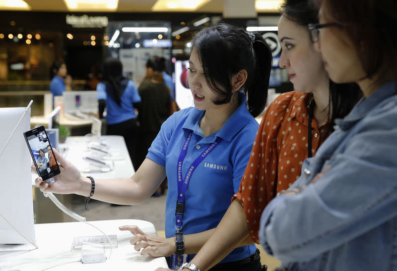 A Samsung salesperson shows a Samsung smartphone to customers at a Samsung showroom in Jakarta