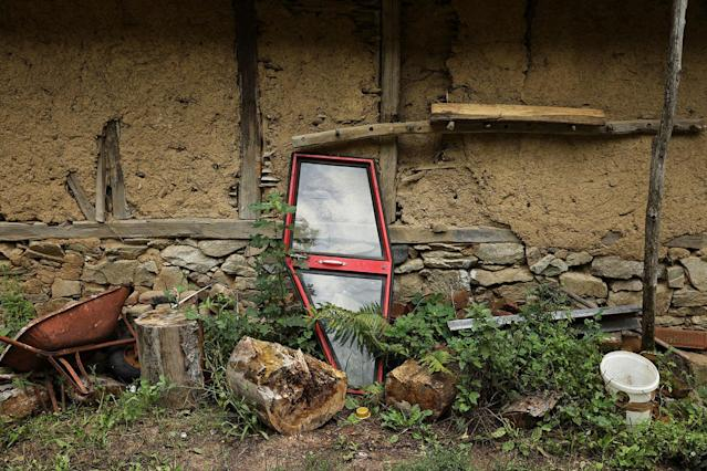 <p>A tractor door is seen in front of an abandoned house in the empty village of Repusnica, near the southeastern town of Knjazevac, Serbia, Aug. 15, 2017. (Photo: Marko Djurica/Reuters) </p>
