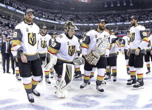 Vegas Golden Knights' James Neal (18), Deryk Engelland (5), goaltender Marc-Andre Fleury (29) and the rest of the team celebrate after defeating the Winnipeg Jets during NHL Western Conference Finals, game 5, in Winnipeg, Sunday, May 20, 2018. (Trevor Hagan/The Canadian Press via AP)