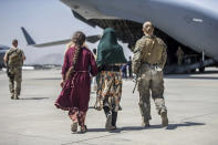 In this image provided by the U.S. Marine Corps, a Marine with the 24th Marine Expeditionary Unit walks with a family during ongoing evacuations at Hamid Karzai International Airport, Kabul, Afghanistan, Tuesday, Aug. 24, 2021. (Sgt. Samuel Ruiz/U.S. Marine Corps via AP)