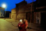 FILE PHOTO: A woman carries a child at night in the old town of Kashgar