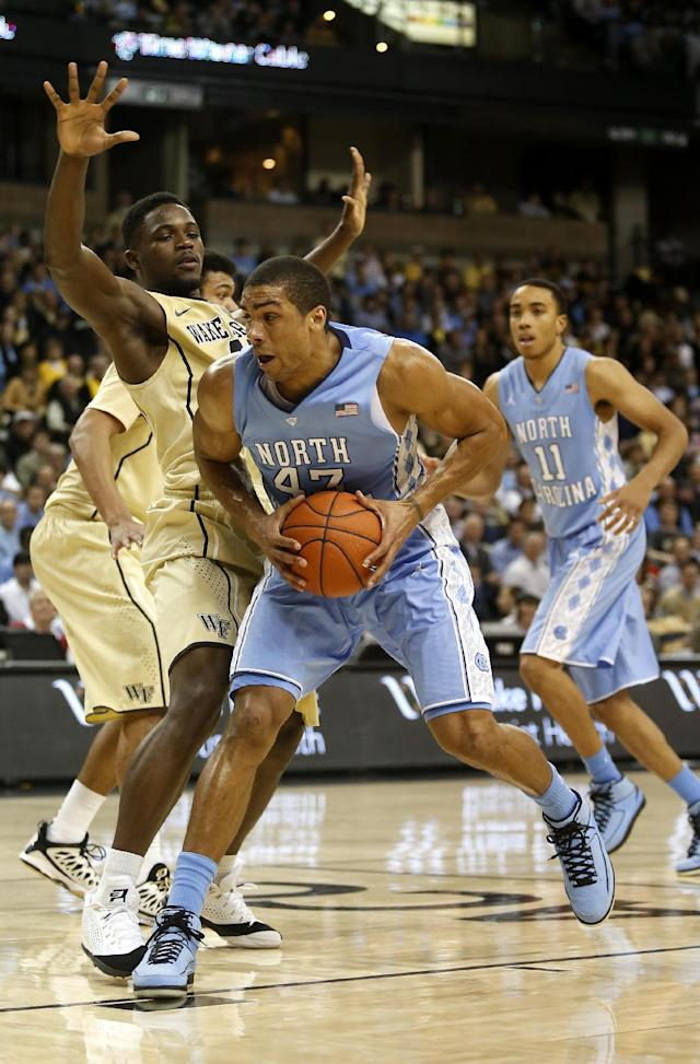 North Carolina forward James Michael McAdoo, right, drives against Wake Forest forward Arnaud William Adala Moto, of Cameroon, in the second half of an NCAA college basketball game, Sunday, Jan. 5, 2014, in Winston-Salem, N.C. Wake Forest won 73-67. (AP Photo/Nell Redmond)