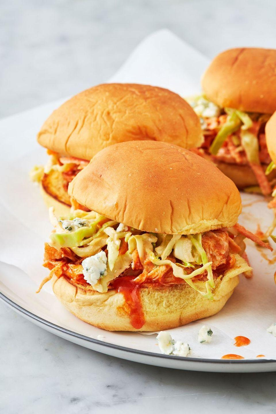 """<p>These sliders are the ultimate crowd pleaser. Served on soft, toasted rolls, the juicy pulled chicken is tossed in hot sauce and topped with fresh crunchy ranch coleslaw and creamy chunks of blue cheese. </p><p>Get the <a href=""""https://www.delish.com/uk/cooking/recipes/a31389657/instant-pot-buffalo-chicken-recipe/"""" rel=""""nofollow noopener"""" target=""""_blank"""" data-ylk=""""slk:Instant Pot Buffalo Chicken Sliders"""" class=""""link rapid-noclick-resp"""">Instant Pot Buffalo Chicken Sliders</a> recipe.</p>"""