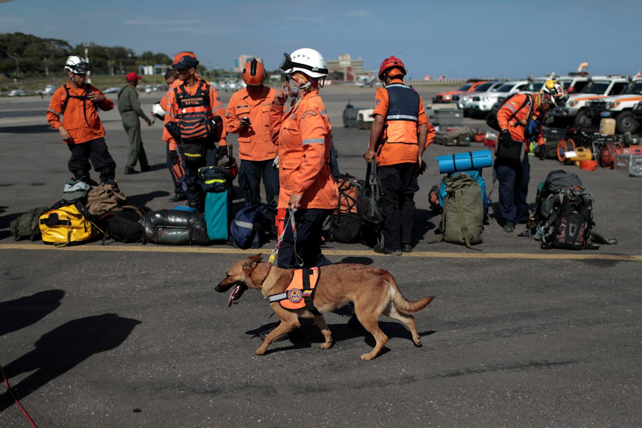 <p>A Venezuelan Civil Protection member walks with a rescue dog as they wait to depart for Mexico to help with the rescue mission after an earthquake in Mexico City, in Caracas, Venezuela on Sept. 20, 2017. (Photo: Marco Bello/Reuters) </p>