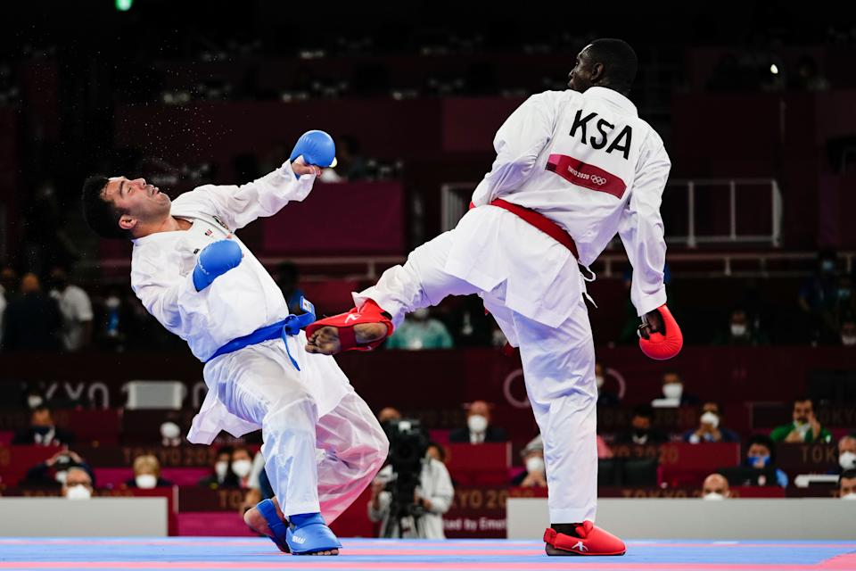 TOKYO, JAPAN - AUGUST 07: Sajad Ganjzadeh (L) of Team Iran gets injured as he competes against Tareg Hamedi of Team Saudi Arabia during the Men's Karate Kumite +75kg Gold Medal Bout on day fifteen of the Tokyo 2020 Olympic Games at Nippon Budokan on August 7, 2021 in Tokyo, Japan. (Photo by Wei Zheng/CHINASPORTS/VCG via Getty Images)