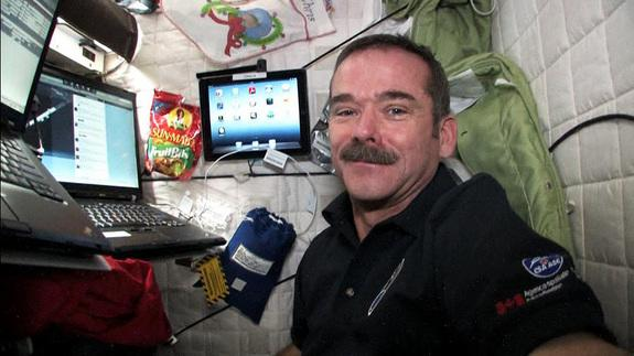 Canadian astronaut Chris Hadfield poses with his computer in the International Space Station on Jan. 11, 2013, He uses the computer to post updates and photos of his Expedition 34/35 mission on Twitter.