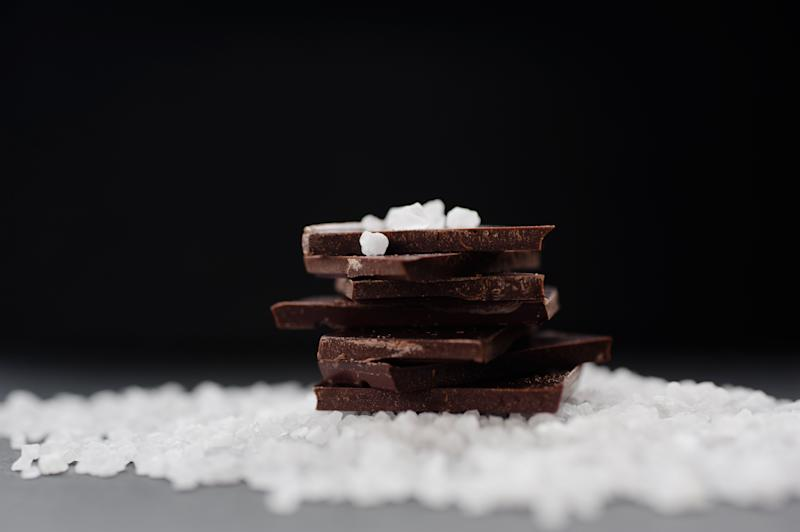 Pile of dark bitter chocolate with sea salt on dark background.