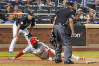 Philadelphia Phillies' Didi Gregorius (18) slides into home to score on a sacrifice fly by Matt Vierling during the seventh inning of the team's baseball game against the New York Mets, Friday, Sept. 17, 2021, in New York. (AP Photo/Mary Altaffer)