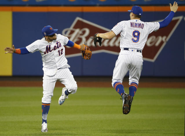 New York Mets center fielder Juan Lagares, left, leaps to celebrate with right fielder Brandon Nimmo (9) after the Mets' 9-0 win over the Arizona Diamondbacks in a baseball game Wednesday, Sept. 11, 2019, in New York. (AP Photo/Kathy Willens)