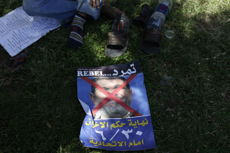"An Egyptian man sits next to a poster of Egypt's Islamist President Mohammed Morsi with Arabic that reads,""June 30, the end of the reign of terror"", ahead of planned mass protests, in front the presidential palace in Cairo, Friday, June 28, 2013. (AP Photo/Hassan Ammar)"