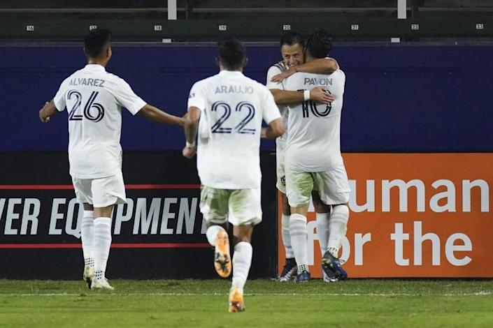 LA Galaxy forward Javier Hernandez, second from right, celebrates with midfielder Efrain Alvarez (26), defender Julian Araujo (22), and forward Cristian Pavon (10) after scoring a goal during the second half of the team's MLS soccer match against the Seattle Sounders on Wednesday, Nov. 4, 2020, in Carson, Calif. (AP Photo/Ashley Landis)