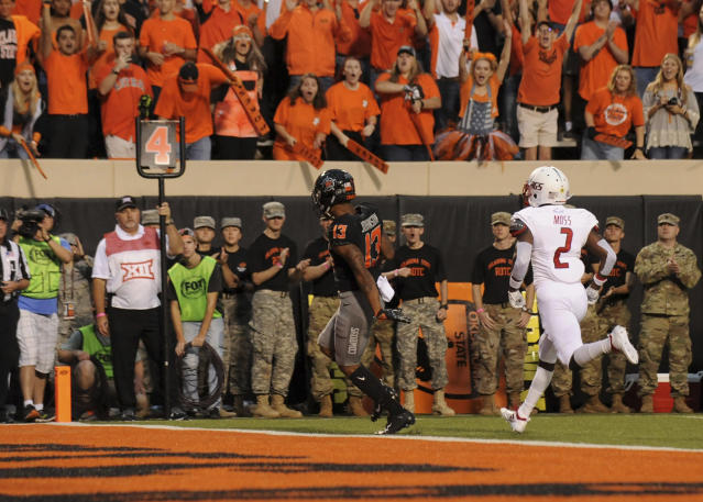 South Alabama safety Tobias Moss (2) chases Oklahoma State wide receiver Tyron Johnson (13) as he scores a touchdown during the first half of an NCAA college football game in Stillwater, Okla., Saturday, Sept. 8, 2018. (AP Photo/Brody Schmidt)