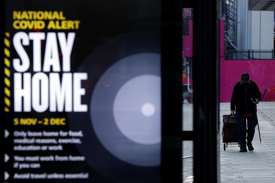 A man walks past a sign displaying the measures imposed by the government against the outbreak of the coronavirus disease (COVID-19), on the first day of a newly imposed lockdown, in London, Britain, November 5, 2020. REUTERS/John Sibley