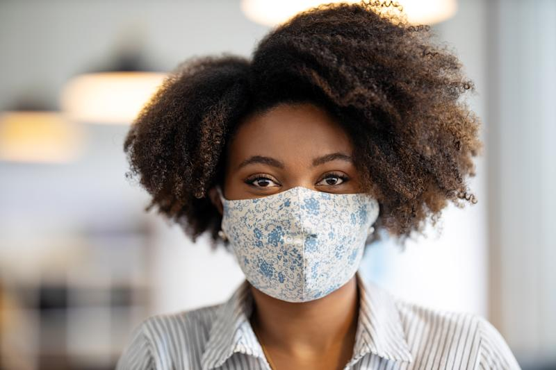 Close-up portrait of an african businesswoman with face mask after returning back to work at office. Woman with protective face mask standing in office and staring at camera.