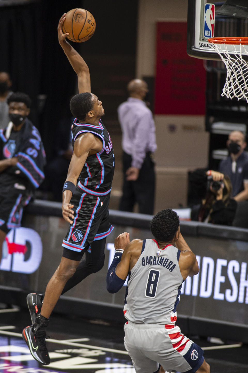 Sacramento Kings guard De'Aaron Fox (5) dunks in front of Washington Wizards forward Rui Hachimura (8) during the second quarter of an NBA basketball game in Sacramento, Calif., Wednesday, April 14, 2021. (AP Photo/Hector Amezcua)