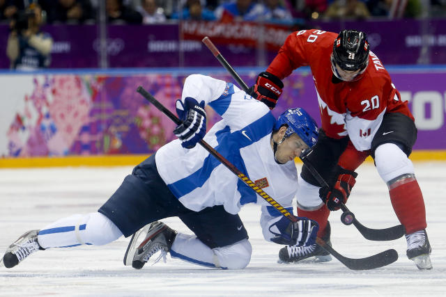Finland forward Jori Lehtera fights Canada forward John Tavares for the puck in the third period of a men's ice hockey game at the 2014 Winter Olympics, Sunday, Feb. 16, 2014, in Sochi, Russia. (AP Photo/Mark Humphrey)