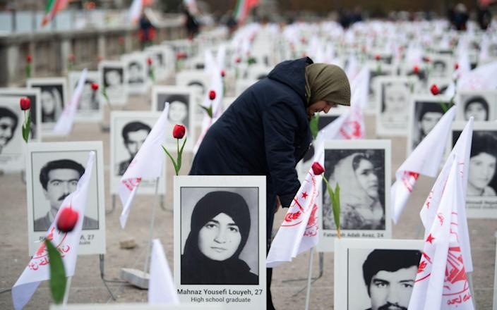 A member of the People's Mujahedin of Iran in France displays portraits of victims on the Esplanade des Invalides in Paris on October 29, 2019 to commemorate the executions of thousands of Iranian political prisoners in 1988 - ERIC FEFERBERG & # xa0;  / AFP