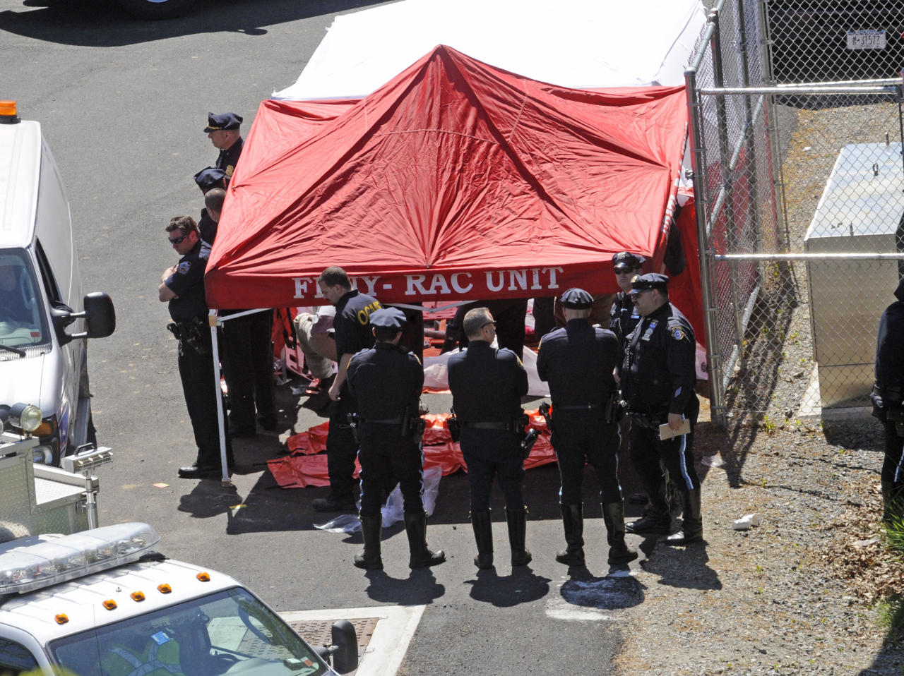 Police surround a temporarily built tent where the victims of a vehicle crash were brought, Sunday April 29, 2012, in New York. Authorities say the out-of-control van plunged off a roadway near the Bronx Zoo, killing seven people, including three children. (AP Photo/ Louis Lanzano)