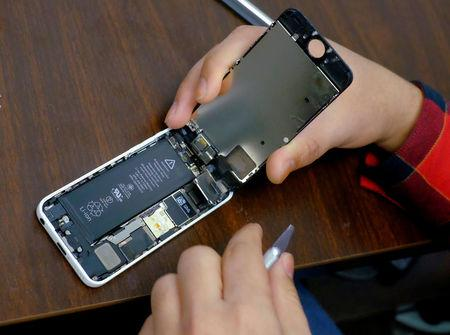 FILE PHOTO: A man tries to repair an iPhone in a repair store in New York