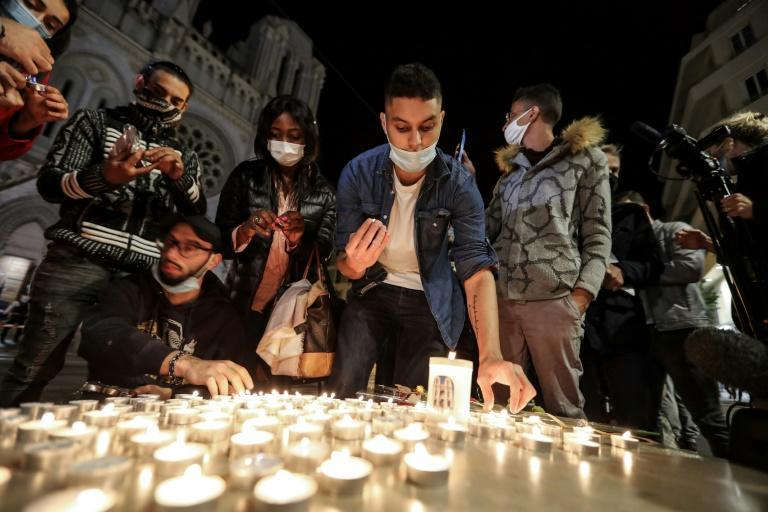 People lights candle outside the Notre-Dame de l'Assomption Basilica in Nice on October 29, 2020 in tribute to the three victims